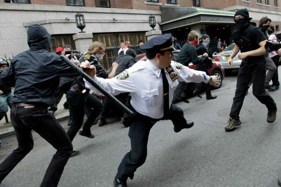 """FILE - In this May 1, 2012, file photo, a police lieutenant swings his baton at Occupy Wall Street activists in New York. This photo is among the many put on Twitter in response to a New York Police Department request for Twitter users to share pictures of themselves posing with police officers. The NYPD sent a tweet on Tuesday, April 22, 2014, saying it might feature the photographs on its Facebook page. The responses soon turned ugly when Occupy Wall Street tweeted a photograph of cops battling protesters with the caption """"changing hearts and minds one baton at a time."""" Similar photos of harsh treatment by the New York City police followed. Photo: Mary Altaffer, AP / AP"""