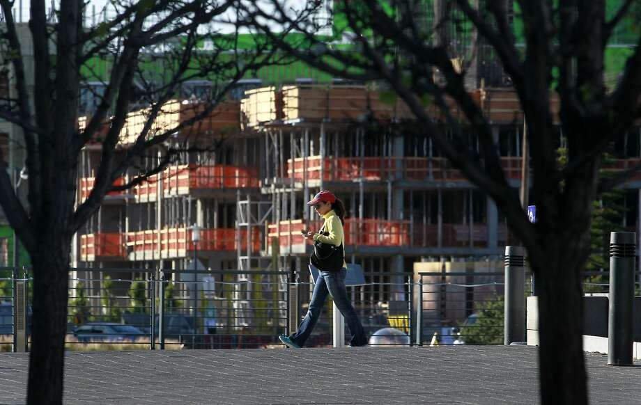A woman walks through Mission Creek Park past one of the many apartment buildings under construction in the Mission Bay area. Photo: Paul Chinn, The Chronicle
