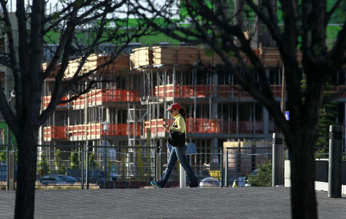 A woman walks on the path at Mission Creek Park across from new apartments under construction in San Francisco, Calif. on Wednesday, April 23, 2014. The new Warriors arena will be built just a few blocks away from the already thriving neighborhood.
