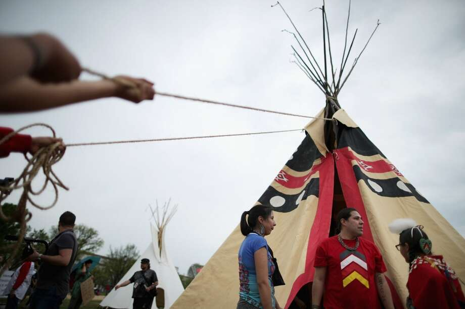 """WASHINGTON, DC - APRIL 22:  Native Americans from various tribes work together to erect a large tepee as part of a demonstration against the proposed Keystone XL pipeline on the National Mall April 22, 2014 in Washington, DC. As part of its """"Reject and Protect"""" protest, the Cowboy and Indian Alliance is organizing a weeklong series of actions by farmers, ranchers and tribes to show their opposition to the pipeline.  (Photo by Chip Somodevilla/Getty Images) Photo: Chip Somodevilla, Getty Images"""