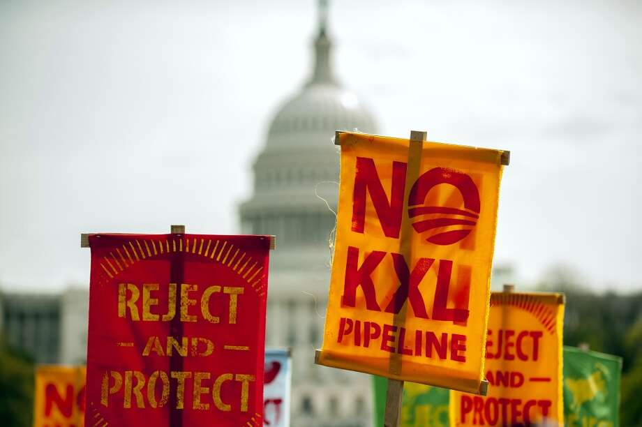 Members of the Cowboy and Indian Alliance, a group of ranchers, farmers and indigenous leaders hold signs during a protest against the Keystone XL pipeline on the National Mall in Washington, D.C. on Tuesday, April 22, 2014. TransCanada Corp. is awaiting a U.S. permit to build the northern leg of Keystone XL, which would supply U.S. Gulf Coast refineries with crude from Alberta's oil sands. Because it crosses an international boundary, the proposal requires State Department approval. Photo: Pete Marovich, Bloomberg