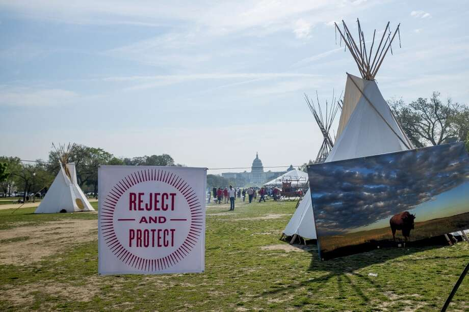 "A ""Reject and Protect"" sign hangs at an encampment set up by the  Cowboy and Indian Alliance (CIA), a group of ranchers, farmers and indigenous leaders during a protest against the Keystone XL pipeline on the National Mall in Washington, D.C., U.S., on Tuesday, April 22, 2014. TransCanada Corp. is awaiting a U.S. permit to build the northern leg of Keystone XL, which would supply U.S. Gulf Coast refineries with crude from Alberta's oil sands. Because it crosses an international boundary, the proposal requires State Department approval. Photographer: Pete Marovich/Bloomberg Photo: Pete Marovich, Bloomberg"
