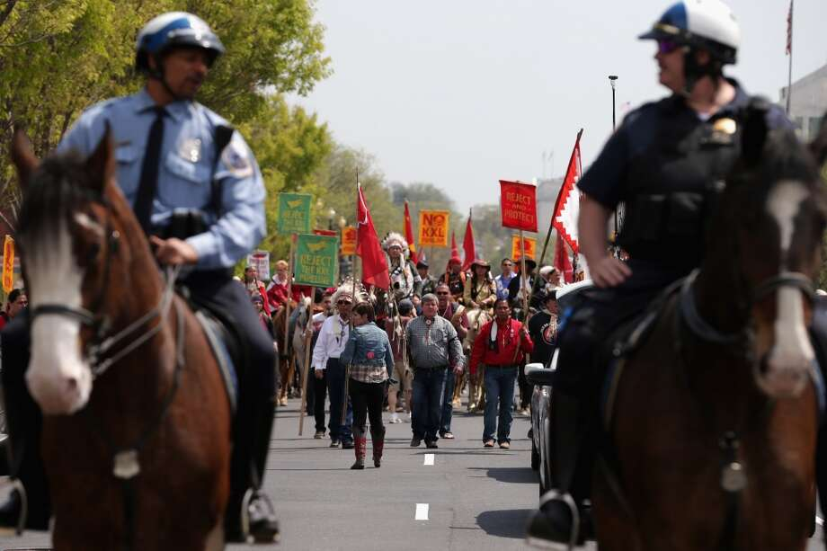 "WASHINGTON, DC - APRIL 22:  Members of the Cowboy and Indian Alliance, including Native Americans, farmers and ranchers from across the United States, are escorted by police as they march down Independence Avenue while demonstrating against the proposed Keystone XL pipeline April 22, 2014 in Washington, DC. As part of its ""Reject and Protect"" protest, the Cowboy and Indian Alliance is organizing a weeklong series of actions by farmers, ranchers and tribes to show their opposition to the pipeline.  (Photo by Chip Somodevilla/Getty Images) Photo: Chip Somodevilla, Getty Images"