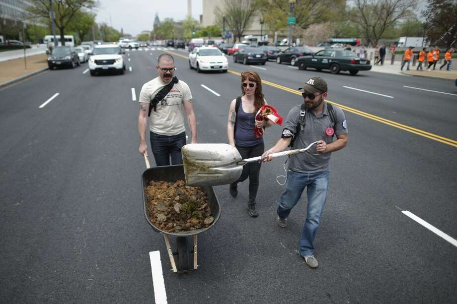 """WASHINGTON, DC - APRIL 22:  (L-R) Farhad Ebrahimi of Boston, Virgina Leavell of the District of Columbia and David Turnbull of San Francisco scoop horse manure up from the middle of Independence Avenue after members of the Cowboy and Indian Alliance rode horseback while demonstrating against the proposed Keystone XL pipeline April 22, 2014 in Washington, DC. As part of its """"Reject and Protect"""" protest, the Cowboy and Indian Alliance is organizing a weeklong series of actions by farmers, ranchers and tribes to show their opposition to the pipeline.  (Photo by Chip Somodevilla/Getty Images) Photo: Chip Somodevilla, Getty Images"""