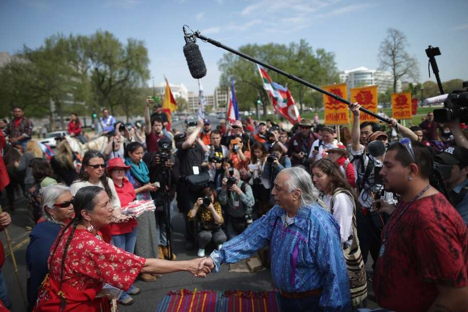 "WASHINGTON, DC - APRIL 22:  Casey Camp of the Ponca Nation (L) shakes hands with Piscataway Indian Nation Chief Billy Redwing Tayac during a traditional opening ceremony to begin a demonstration against the proposed Keystone XL pipeline at the U.S. Capitol Reflecting Pool on the National Mall April 22, 2014 in Washington, DC. As part of its ""Reject and Protect"" protest, the Cowboy and Indian Alliance is organizing a weeklong series of actions by farmers, ranchers and tribes to show their opposition to the pipeline.  (Photo by Chip Somodevilla/Getty Images) Photo: Chip Somodevilla, Getty Images"