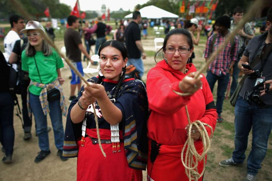"""WASHINGTON, DC - APRIL 22:  (L-R) Samantha Jones (L) of the Sicangu Lakota Band of the Rosebud Sioux Tribe from Rosebud, South Dakota and Brandie Molina help raise a large tepee as part of a demonstration against the proposed Keystone XL pipeline on the National Mall April 22, 2014 in Washington, DC. As part of its """"Reject and Protect"""" protest, the Cowboy and Indian Alliance is organizing a weeklong series of actions by farmers, ranchers and tribes to show their opposition to the pipeline.  (Photo by Chip Somodevilla/Getty Images) Photo: Chip Somodevilla, Getty Images"""