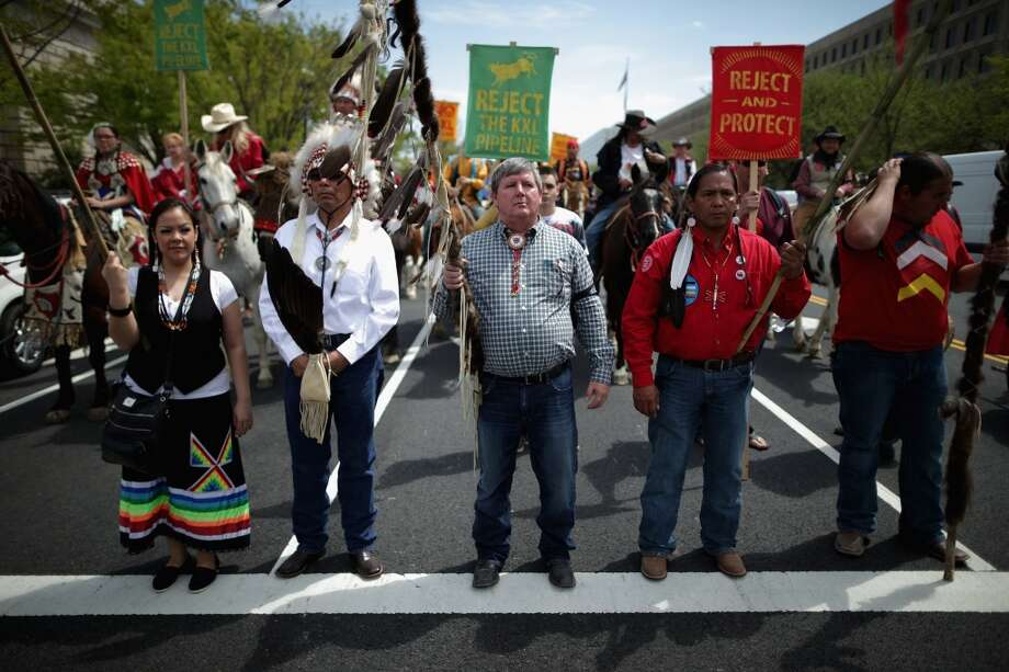 """WASHINGTON, DC - APRIL 22:  Members of the Cowboy and Indian Alliance, including Native American tribal leaders and non-native farmers and ranchers from across the United States, march down Independence Avenue while demonstrating against the proposed Keystone XL pipeline April 22, 2014 in Washington, DC. As part of its """"Reject and Protect"""" protest, the Cowboy and Indian Alliance is organizing a weeklong series of actions by farmers, ranchers and tribes to show their opposition to the pipeline.  (Photo by Chip Somodevilla/Getty Images) Photo: Chip Somodevilla, Getty Images"""