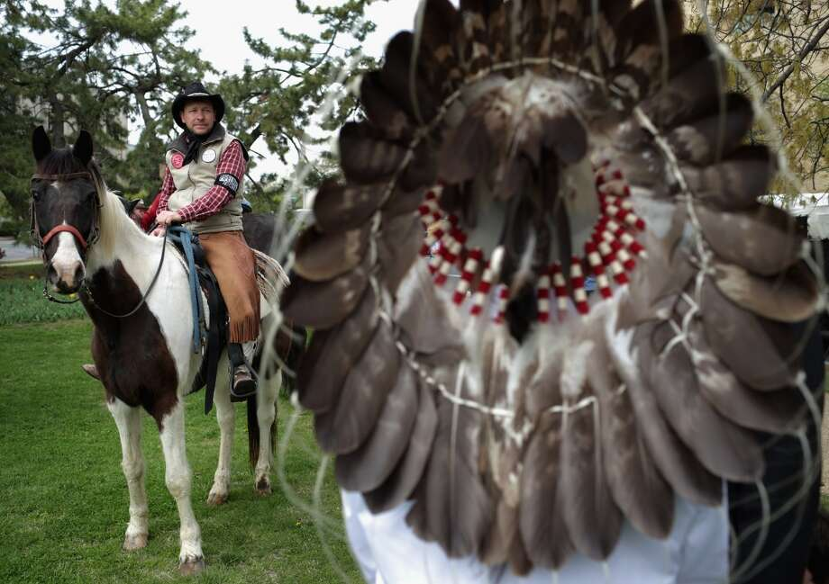"""WASHINGTON, DC - APRIL 22:  Members of the Cowboy and Indian Alliance, including Native Americans, farmers and ranchers from across the United States, prepare for a horseback ride to demonstrate against the proposed Keystone XL pipeline in front of the U.S. Capitol April 22, 2014 in Washington, DC. As part of its """"Reject and Protect"""" protest, the Cowboy and Indian Alliance is organizing a weeklong series of actions by farmers, ranchers and tribes to show their opposition to the pipeline.  (Photo by Chip Somodevilla/Getty Images) Photo: Chip Somodevilla, Getty Images"""