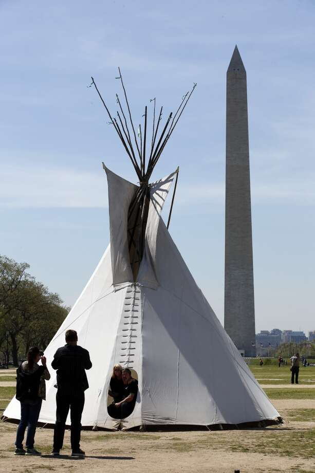 "Paula-May Belous, left, and her husband Michael Belous, both from Brisbane, Australia, pose in the door of a teepee on the National Mall in Washington, Monday, April 21, 2014, with the Washington Monument in the background. The Cowboy and Indian Alliance (CIA), a group of ranchers, farmers and indigenous leaders, will host an encampment on the National Mall for a week's worth of ""Reject and Protect"" actions against the Keystone XL tar sands pipeline. (AP Photo/Alex Brandon) Photo: Alex Brandon, Associated Press"