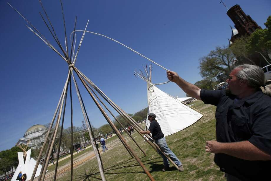 "Matt Buban, right, and Ben Thompson, both from from Charles Town, W.Va., with One Heart One Mind, set up teepee poles on the National Mall in Washington, Monday, April 21, 2014. The Cowboy and Indian Alliance (CIA), a group of ranchers, farmers and indigenous leaders, will host an encampment on the National Mall for a week's worth of ""Reject and Protect"" actions against the Keystone XL tar sands pipeline. (AP Photo/Alex Brandon) Photo: Alex Brandon, Associated Press"