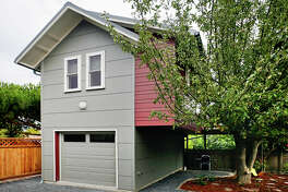 "Falcon's Nest, 7744 Dibble Ave. N.W., by Red Cottage Studios. This backyard cottage is for out-of-town grandparents to use when visiting Seattle. It includes air sealing of every outlet and light switch, plus a one-inch ""flash coat"" of closed-cell foam sprayed into the advanced-framed walls, formaldehyde-free fiberglass insulation in the ceiling and floors, plumbing designed to be drained so the building doesn't need to be heated when it's empty, light colored and reflective finishes to make the most of the light from south-facing windows, low-formaldehyde particle board cabinets, no-fume paint, a deck in the branches of an old apple tree, a rock reservoir that holds storm water from the driveway, and cisterns to collect water from the roof."