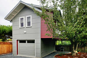 """Falcon's Nest, 7744 Dibble Ave. N.W. , by Red Cottage Studios. This backyard cottage is for out-of-town grandparents to use when visiting Seattle. It includes air sealing of every outlet and light switch, plus a one-inch """"flash coat"""" of closed-cell foam sprayed into the advanced-framed walls, formaldehyde-free fiberglass insulation in the ceiling and floors, plumbing designed to be drained so the building doesn't need to be heated when it's empty, light colored and reflective finishes to make the most of the light from south-facing windows, low-formaldehyde particle board cabinets, no-fume paint, a deck in the branches of an old apple tree, a rock reservoir that holds storm water from the driveway, and cisterns to collect water from the roof."""
