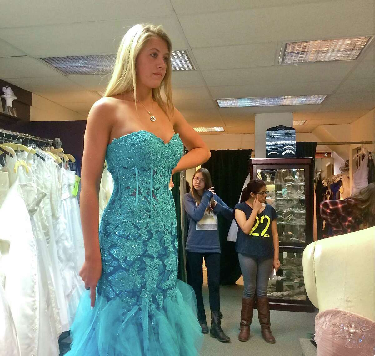Mandy Thompson, a senior at New Fairfield HIgh School, tries on a mermaid-style gown at Occasions Bridal Shop in Bethel.