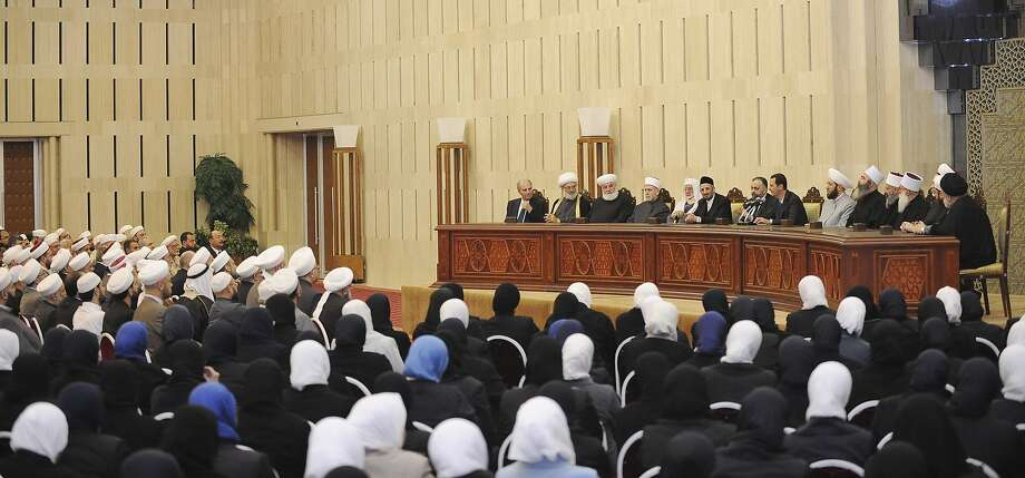 Syria's President Bashar al-Assad (8th R, seated) attends a meeting with clergymen and preachers in Damascus April 23, 2014, in this handout photograph released by Syria's national news agency SANA. REUTERS/SANA/Handout via Reuters (SYRIA - Tags: POLITICS RELIGION CONFLICT CIVIL UNREST) ATTENTION EDITORS - THIS PICTURE WAS PROVIDED BY A THIRD PARTY. REUTERS IS UNABLE TO INDEPENDENTLY VERIFY THE AUTHENTICITY, CONTENT, LOCATION OR DATE OF THIS IMAGE. THIS PICTURE IS DISTRIBUTED EXACTLY AS RECEIVED BY REUTERS, AS A SERVICE TO CLIENTS. FOR EDITORIAL USE ONLY. NOT FOR SALE FOR MARKETING OR ADVERTISING CAMPAIGNS Photo: Sana, Reuters
