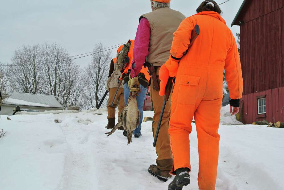 FILE - Joe Messina, second from right, carries a pheasant from the day's hunt and retreats with other hunters to the house on his Valley Falls winery. (Deanna Fox)