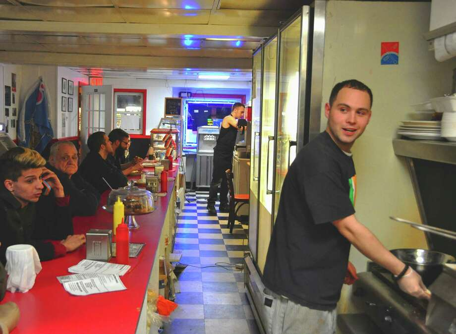 Steve Barnes/Times Union  Alex Portelli, owner of Portelli's Joe N' Dough Cafe on lower Central Avenue in Albany, cooks and serves to an overnight crowd looking for  greasy-spoon fare with a homemade touch.
