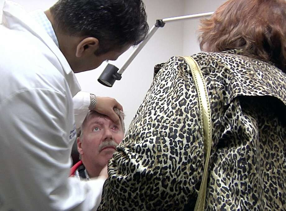 Dr. Thiran Jayasundera examines Roger Pontz's eye as Pontz's wife, Terri, looks on at the Kellogg Eye Center in Michigan. Photo: Mike Householder, Associated Press