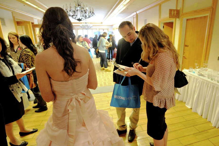 Darya Sipyekina and her fiance Eugene Viderman attend the Dolce Bridal Show as a model walks by in a wedding dress at Dolce Norwalk in Norwalk, Conn., on Sunday, April 6, 2014. Photo: Jason Rearick / Stamford Advocate