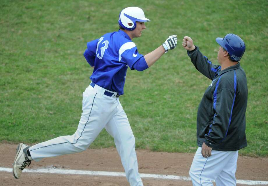 Bunnell's Ronnie Rossomando gets congratulated by Head Coach Scott Szturma after hitting a two run home run in Bunnell's win over Pomperaug in the high school baseball game at Pomperaug High School in Southbury, Conn. Tuesday, April 22, 2014. Photo: Tyler Sizemore / The News-Times