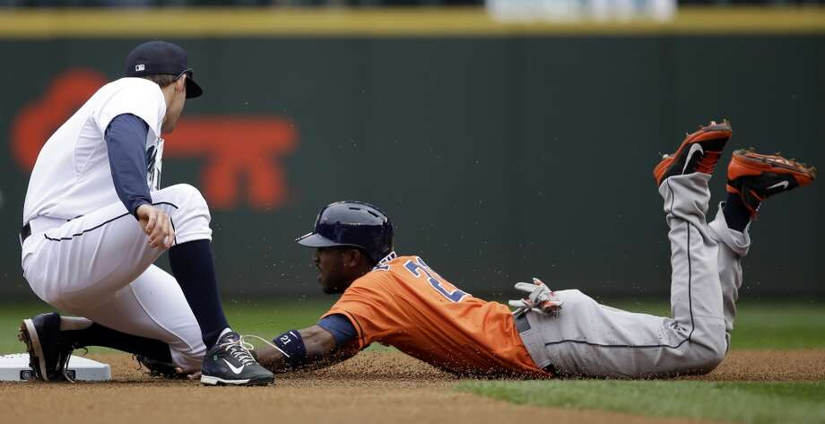 Dexter Fowler, right, slides into a tag for an out by Mariners shortstop Brad Miller in the first inning. Photo: Elaine Thompson, Associated Press