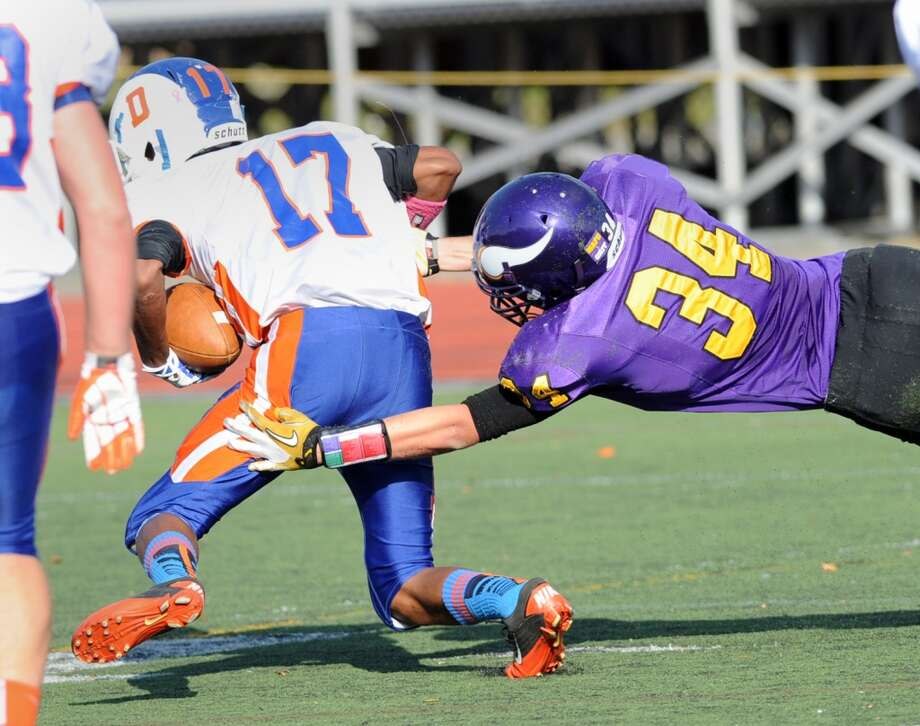 At right, Westhill's Joe Schlessinger (# 34) takes down Danbury's Matt Andrew (# 17) during the high school football game between Westhill High School and Danbury High School at Westhill High School in Stamford, Saturday, Nov. 2, 2013. Photo: Bob Luckey
