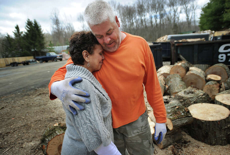 Haydee and Bob Lombard hug as Bob takes a break from splitting wood outside their rental home on Pepper street in Monroe, Conn. on Wednesday, April 23, 2014. The couple, who are also raising their grandson, struggle to make ends meet on Haydee's post office pension and the sale of firewood, which they also use to heat their residenence. Photo: Brian A. Pounds / Connecticut Post