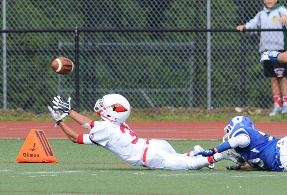 At left, Austin Longi (# 3) of Greenwich stretches-out on an attempted reception during the high school football game between Darien High School and Greenwich High School at Darien, Saturday, Sept. 21, 2013. Although Longi was unable to make the catch, pass interference was called against Darien. Darien defeated Greenwich,42-21. Photo: Bob Luckey