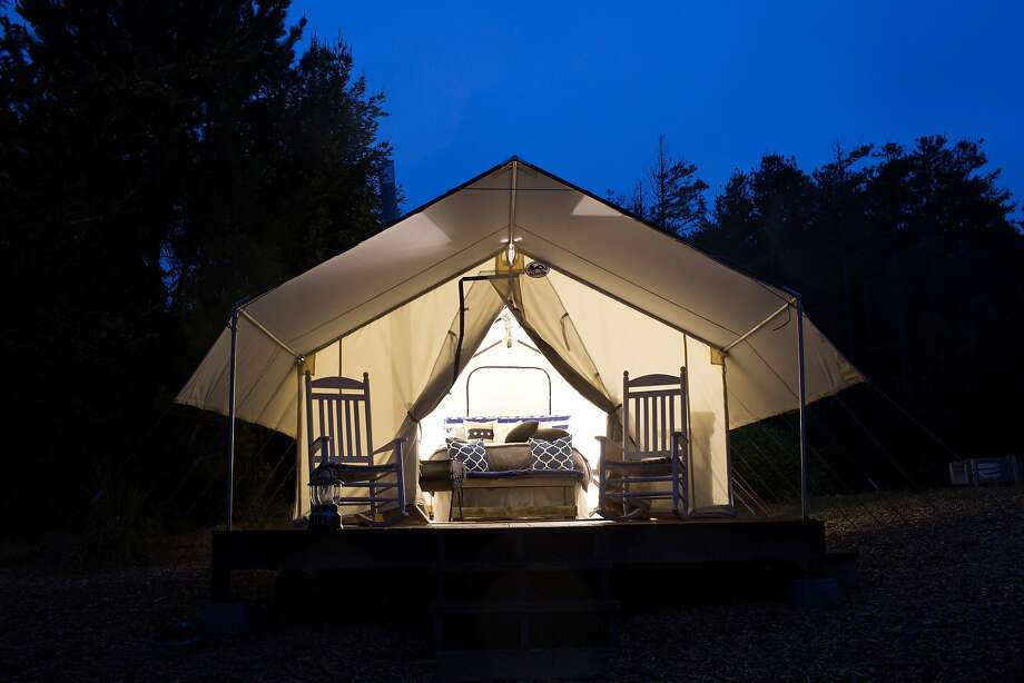 The tents, above, use batterypowered lanterns, have a front porch with rocking chairs and, below, beds with Egyptian cotton sheets. Photo: Jason Henry, Special To The Chronicle
