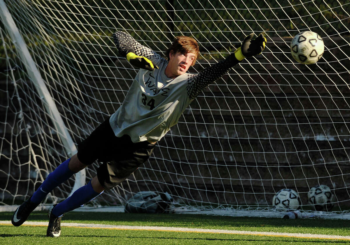 On a direct free kick from Westhill's Filosmar Cordeiro, Darien goalie Liam Rischmann dives unsuccessfully for the ball scoring the Vikings' first goal of their game against the Blue Wave at Westhill High School in Stamford, Conn., on Wednesday, Sept. 18, 2013. Westhill beat Darien, 4-1.