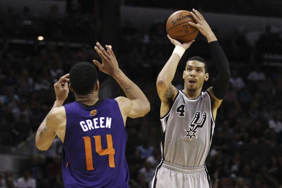 Spurs' Danny Green (04) shoots a three-pointer against Phoenix Suns' Gerald Green (14) in the second half at the AT&T Center on Friday, Apr. 11, 2014. Spurs defeated the Suns, 112-104, and clinches home court advantage throughout the playoffs. Green scored a career high 33 points in addition to seven three pointers. Photo: Kin Man Hui, San Antonio Express-News