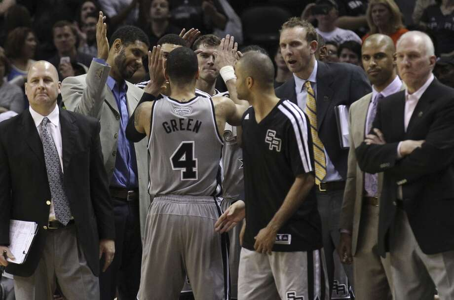 Spurs' Danny Green (04) gets congratulated by the bench including Tim Duncan after he goes off the floor after scoring a career-high 33 points against the Phoenix Suns in the second half at the AT&T Center on Friday, Apr. 11, 2014. Spurs defeated the Suns, 112-104, and clinches home court advantage throughout the playoffs. Photo: Kin Man Hui, San Antonio Express-News