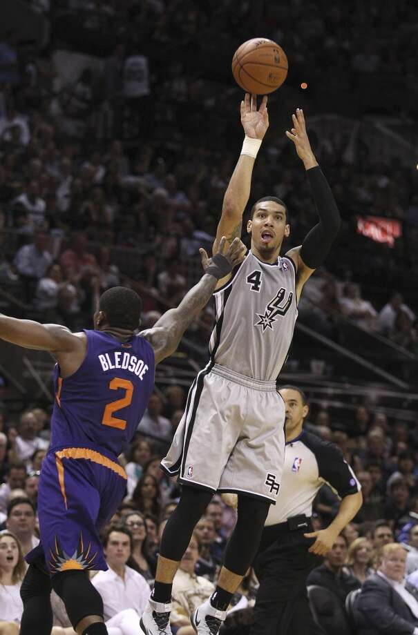 Spurs' Danny Green (04) shoots a three-pointer over Phoenix Suns' Eric Bledsoe (02) in the second half at the AT&T Center on Friday, Apr. 11, 2014. Spurs defeated the Suns, 112-104, and clinches home court advantage throughout the playoffs. Green scored a career-high 33 points along with seven three pointers to give the Spurs the victory. Photo: Kin Man Hui, San Antonio Express-News