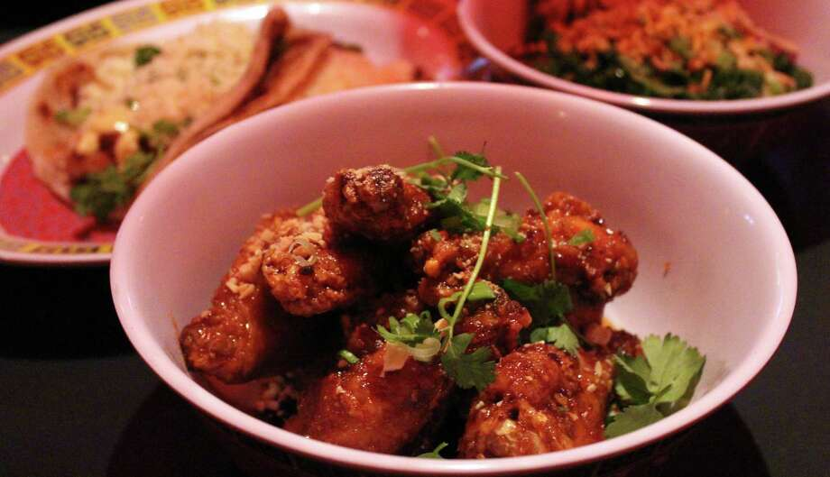 Twice-fried chicken wings  with crab fat caramel, peanuts and cilantro are offered at Hot Joy. Photo: Photos By Jennifer McInnis / San Antonio Express-News