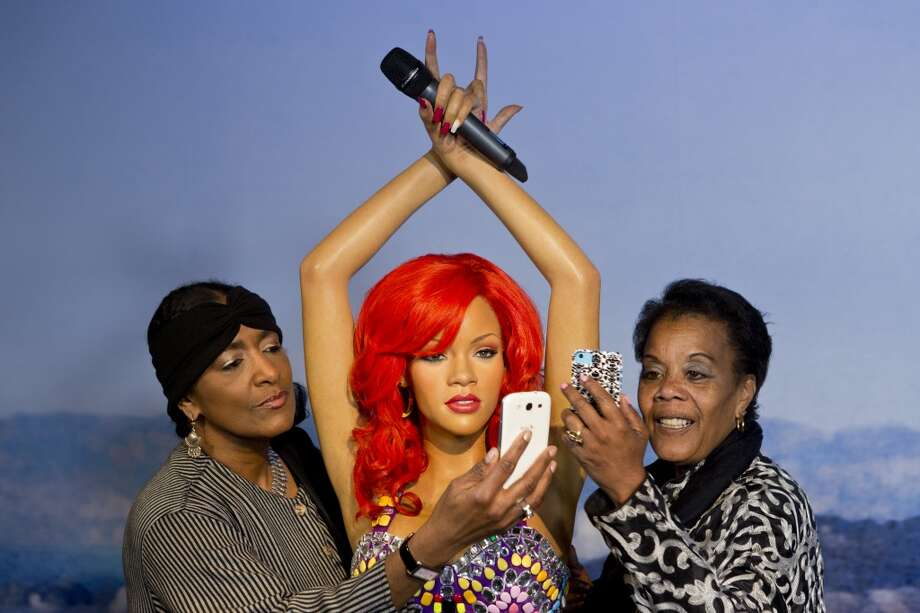 "Karmen Bell (right) of the San Francisco Travel Association and Trevar Booker (left) of the Fisherman's Warf Association  take a ""selfie"" with a wax figure of Rihanna on display at the future site of Madame Tussaud's attraction in San Francisco's Fisherman's Warf on Wednesday April 23, 2014. Photo: Beck Diefenbach, Beck Diefenbach/Madame Tussauds"