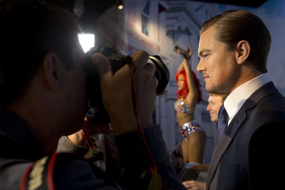 A photographer gets up close and personal with a wax figure of Leonardo DiCaprio on display at the future site of Madame Tussaud's attraction in San Francisco's Fisherman's Warf on Wednesday April 23, 2014. Photo: Beck Diefenbach, Beck Diefenbach/Madame Tussauds