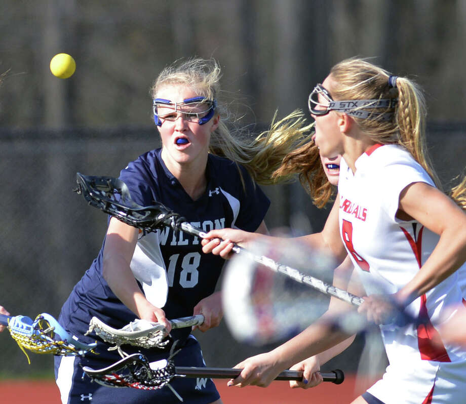 At left, Laura Knapp (#18) of Wilton goes for a loose ball along with Emily Ludington (#8) of Greenwich, at right, during the girls high school lacrosse match between Greenwich High School and Wilton High School at Greenwich, Wednesday, April 23, 2014. Wilton defeated Greenwich by a score of 11-5. Photo: Bob Luckey / Greenwich Time