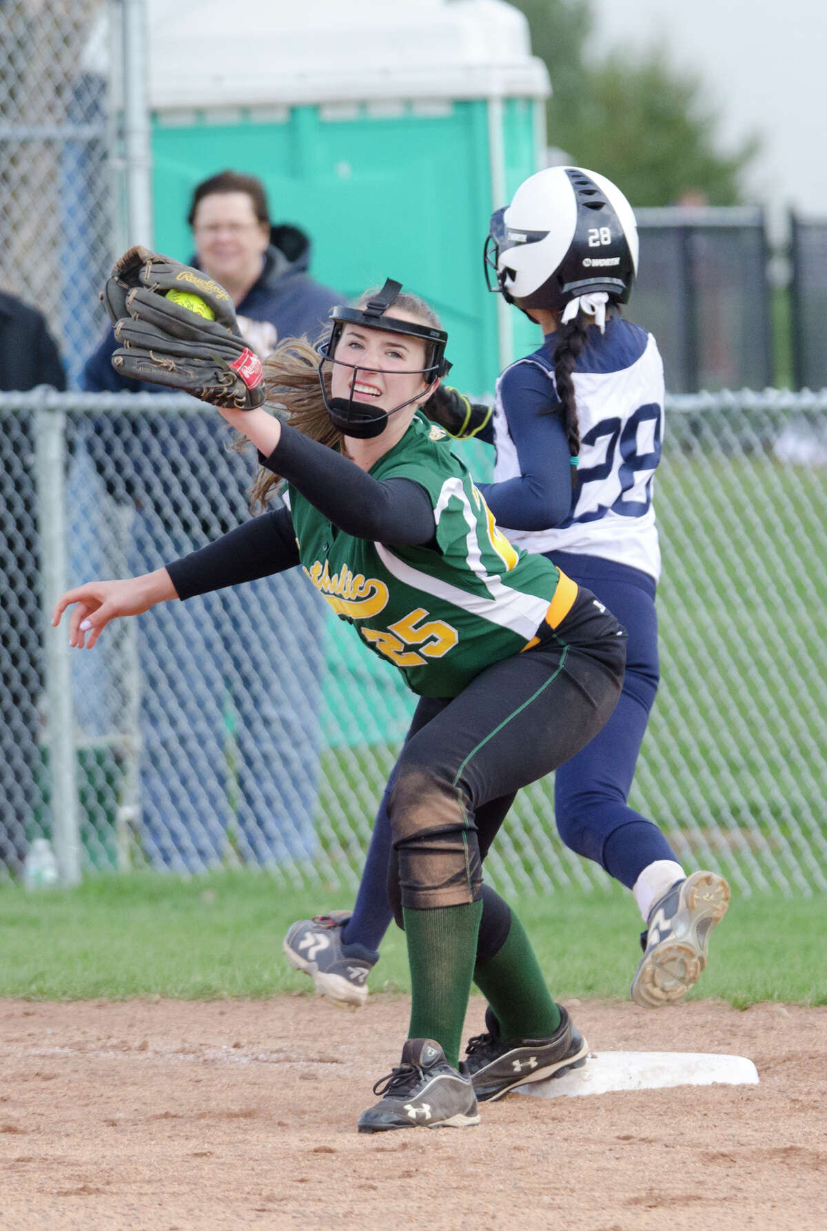 Trinity Catholic's Emily Ellis (25) makes an out as Staples' Chrstine McCarthy (28) runs to first base during the softball game at Wakeman Field in Westport on Wednesday, Apr. 23, 2014.