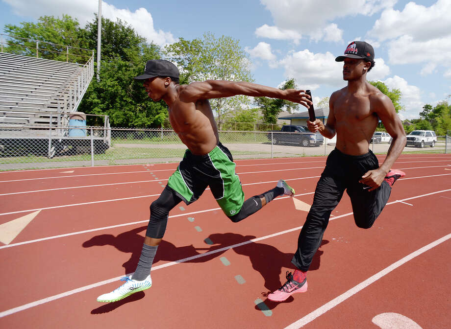 James Reed, left, and Isaiah Wilkerson practice their handoff Wednesday afternoon. West Brook High School's relay team -- Isaiah Wilkerson, Justen Hervey, Cameron McKinney, and James Reed -- poses for a picture at the school's track on Tuesday afternoon. The team won the 400-meter relay at the 21-5A track meet. Photo taken Tuesday, 4/22/14 Jake Daniels/@JakeD_in_SETX Photo: Jake Daniels / ©2014 The Beaumont Enterprise/Jake Daniels