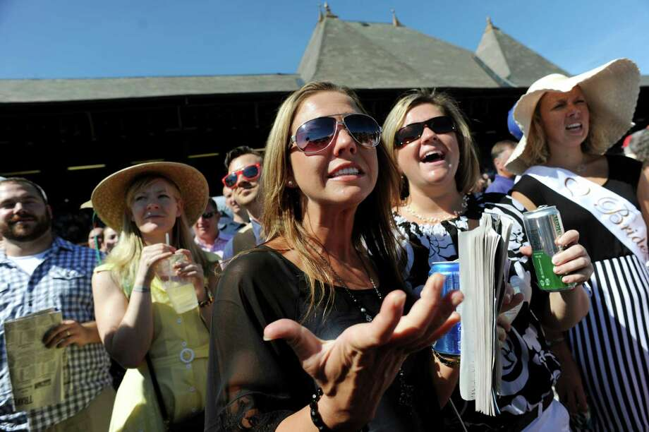 Tiffany Macey of South Glens Falls, center, reacts as her horse falls behind in the 7th race on Travers Day on Saturday, Aug. 24, 2013, at Saratoga Race Course in Saratoga Springs, N.Y. Joining her are friends Megan Tierney of South Glens Falls, second from right, and bride-to-be Alex Matthews of Gansvoort, right. The ladies were there for Matthews' bachelorette party. (Cindy Schultz / Times Union) Photo: Cindy Schultz / 00023621A