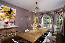The formal dining room is illuminated by a chandelier and features lacquered walls.