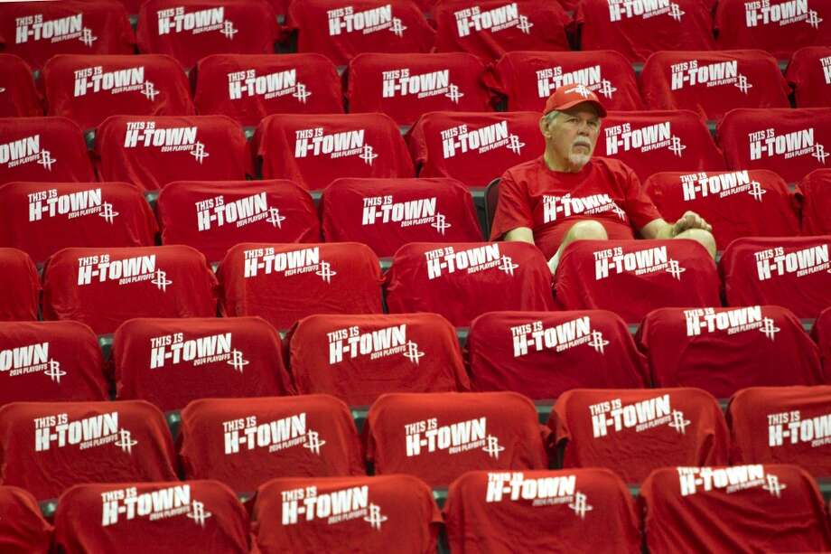 "A Houston Rockets fan sits surrounded by ""H-Town"" t-shirts before Game 1 of the NBA Western Conference Quarterfinal basketball playoff game against the Portland Trail Blazers at Toyota Center Sunday, April 20, 2014, in Houston. ( Brett Coomer / Houston Chronicle ) Photo: Brett Coomer, Houston Chronicle"