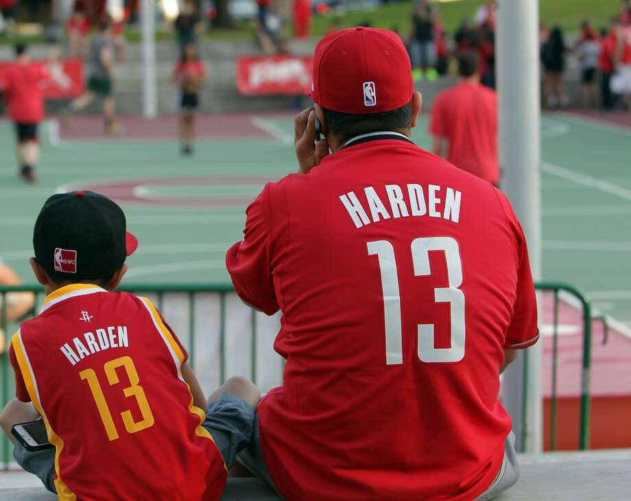 Eight-year-old Joshua Montano left, and his father Mario Montano watch pre-game festivities outside the Toyota Center before game one of the Western Conference Quarterfinals playoff game Sunday, April 20, 2014, in Houston. ( James Nielsen / Houston Chronicle ) Photo: James Nielsen, Houston Chronicle