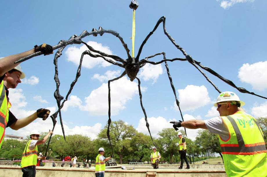 Employees with Ty-art Art Handling Service install the bronze sculpture, Spider, into the cascade of the Jones Reflection Pool at Hermann Park Wednesday, April 23, 2014, in Houston. Photo: Melissa Phillip, Houston Chronicle / © 2014  Houston Chronicle