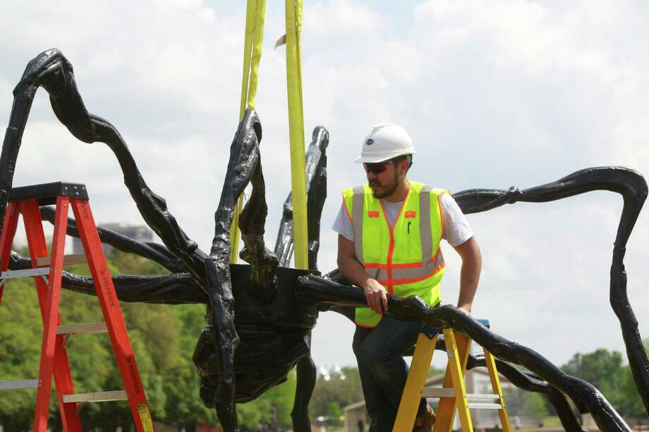 Ike Theriot with Ty-art Art Handling Service works on installation of the bronze sculpture, Spider, in the cascade of the Jones Reflection Pool at Hermann Park Wednesday, April 23, 2014, in Houston. Photo: Melissa Phillip, Houston Chronicle / © 2014  Houston Chronicle