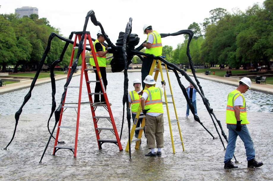Employees with Ty-art Art Handling Service install the bronze sculpture, Spider, in the cascade of the Jones Reflection Pool at Hermann Park Wednesday, April 23, 2014, in Houston. Photo: Melissa Phillip, Houston Chronicle / © 2014  Houston Chronicle