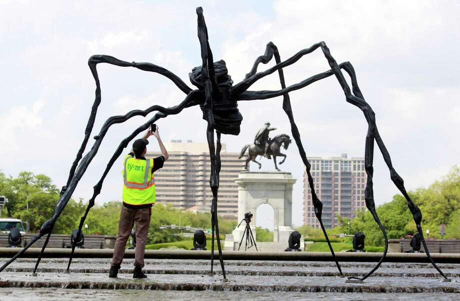 After installation, an employee with Ty-art Art Handling Service photographs the bronze sculpture, Spider, in the cascade of the Jones Reflection Pool at Hermann Park Wednesday, April 23, 2014, in Houston. Photo: Melissa Phillip, Houston Chronicle / © 2014  Houston Chronicle