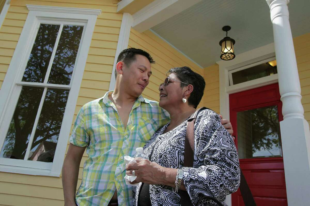 Dominic Yap, a developer who is buying old homes in the First Ward but remodeling them instead of tearing them down hugs Gloria Perez in front of her childhood home he purchased from Perez and remodeled Friday, April 4, 2014, in Houston. Perez sold the house to Yap, instead of another developer, because she didn't want the home torn down.