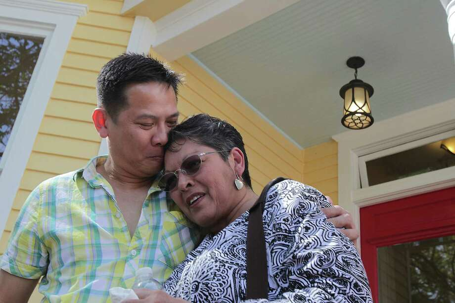 Dominic Yap, a developer who is buying old homes in the First Ward but remodeling them instead of tearing them down hugs Gloria Perez in front of her childhood home he purchased from Perez and remodeled Friday, April 4, 2014, in Houston. Perez sold the house to Yap, instead of another developer, because she didn't want the home torn down. Photo: James Nielsen, Houston Chronicle / © 2014  Houston Chronicle