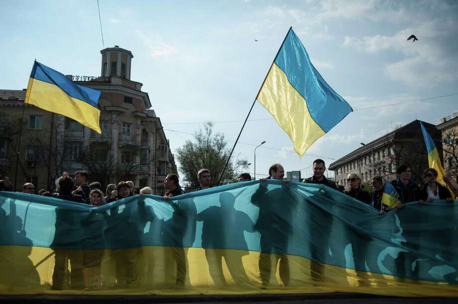 Pro-Ukrainian supporters hold a giant Ukrainian flag during a rally in the southern Ukrainian city of Mariupol, Ukraine, Wednesday, April 23, 2014. Ukraine's announcement that it was resuming operations against pro-Russia forces that have seized police stations and government buildings in the east hasn't produced any reported action on the ground, but brought forth foreboding words from Moscow on Wednesday. (AP Photo/Evgeniy Maloletka) ORG XMIT: XAZ106 Photo: Evgeniy Maloletka / AP