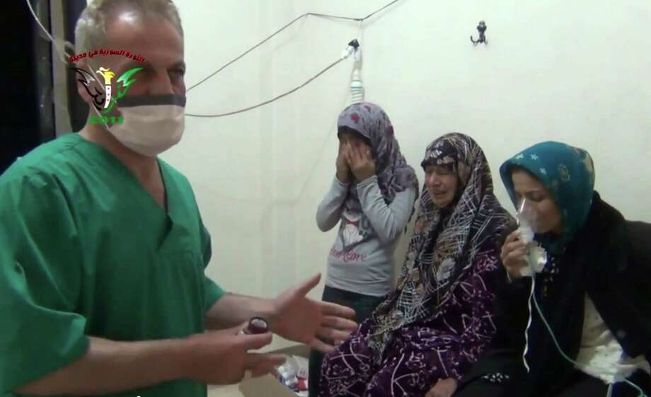 In this image taken from video obtained from the Shaam News Network, posted on April 18, 2014, an anti-Bashar Assad activist group, which has been authenticated based on its contents and other AP reporting, two women and a young girl are treated by a medic in Kfar Zeita, a rebel-held village in Hama province some 200 kilometers (125 miles) north of Damascus. Syrian opposition activists and other witnesses tell The Associated Press that Syrian government forces have attacked rebel-held areas with poisonous chlorine gas in recent months. They say the attacks left scores of men, women and children coughing, choking and gasping for breath. The reports have been denied by the Syrian government and have yet to be confirmed by any foreign country or international organization. But if true, they highlight the limitations of the global effort to rid Syria of its chemical weapons. (AP Photo/Shaam News Network) ORG XMIT: CAI124 Photo: Uncredited / Shaam News Network
